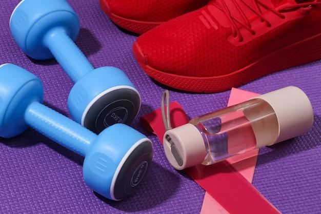 赤いスポーツシューズ、ボトルの水、ダンベル、紫色のスポーツマットのフィットネス輪ゴム。ワークアウトの概念。