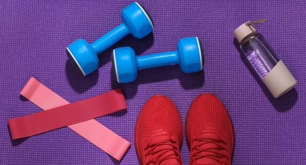 赤いスポーツシューズ、ダンベル、フィットネスの輪ゴム、紫色のスポーツマットの上の水のボトル。ワークアウトの概念。