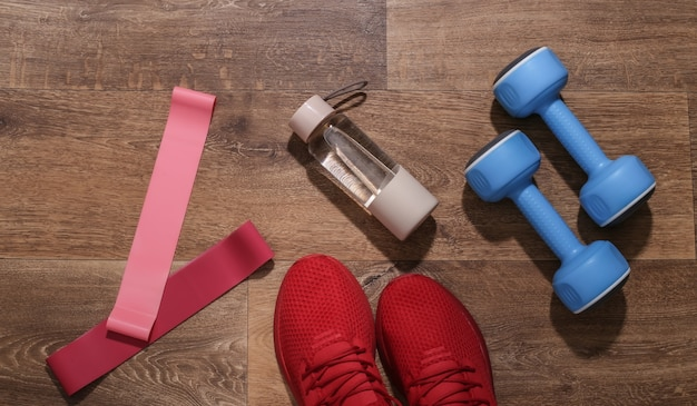 赤いスポーツシューズ、ダンベル、フィットネスの輪ゴム、木の床に水のボトル。ワークアウトの概念