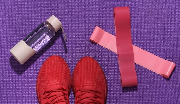 赤いスポーツシューズ、フィットネスの輪ゴム、紫色のスポーツマットの上の水のボトル。ワークアウトの概念。