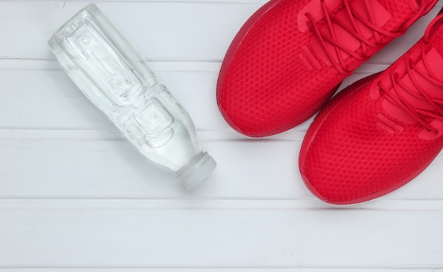 Красная спортивная обувь для бега, бутылка воды на белом деревянном полу. вид сверху.