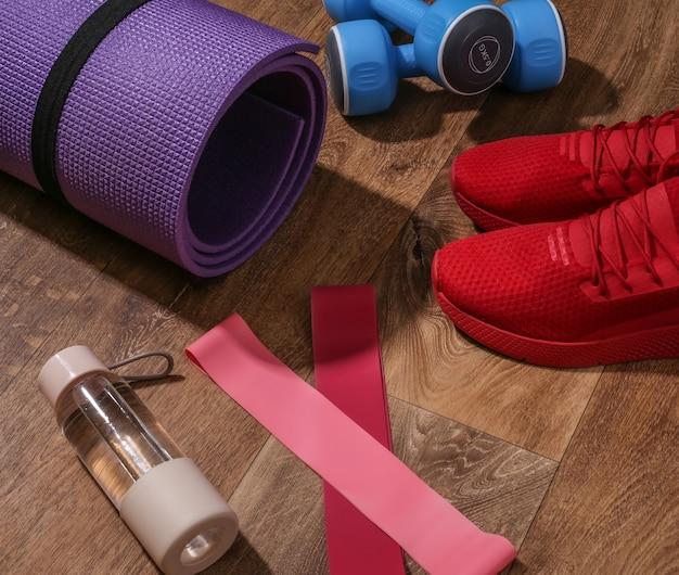 赤いスポーツシューズ、マット、ダンベル、フィットネスの輪ゴム、木の床に水のボトル。ワークアウトの概念