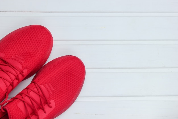 Red sports shoes for running on white wooden floor.