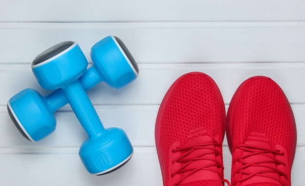 Red sports shoes for training, dumbbells  on white wooden floor. top view.