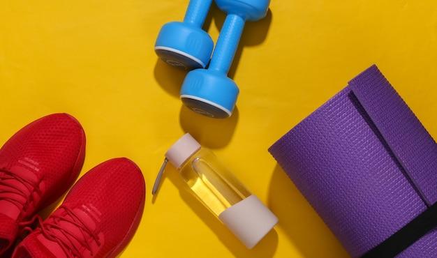深い影のある黄色の明るい背景に赤いスポーツシューズ、水筒、ダンベル、ヨガマット。フィットネス構成。フラットレイ。