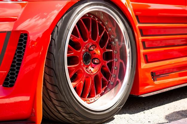 ホイールの赤いスポーツチューンドカーリアビュー、クローズアップ。道路上のファッションカーの日
