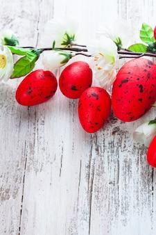Красные пятнистые яйца с яблочными цветами на ветхом деревянном столе