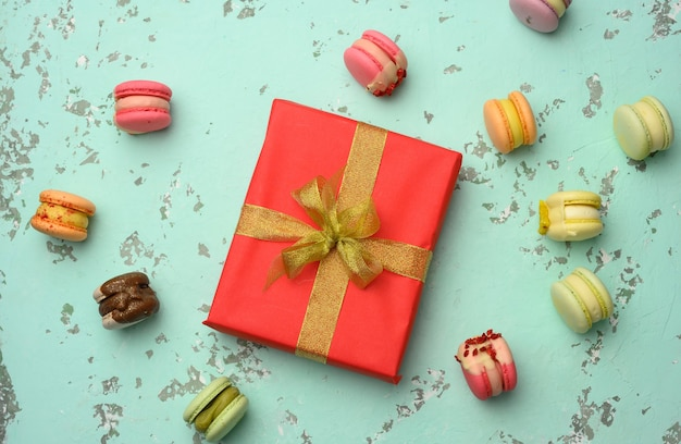 Red square gift box with a bow and baked macarons on a green background, top view