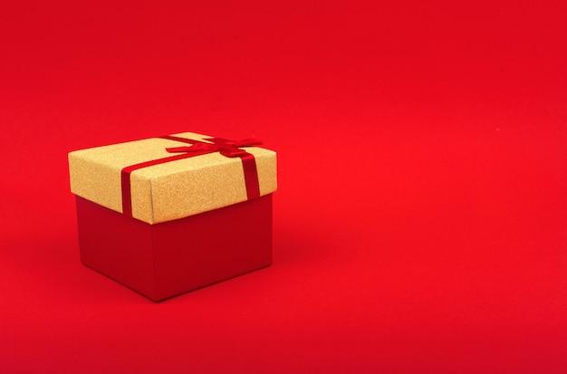 Красная квадратная подарочная коробка с золотой крышкой на красном фоне, минимализм, новогодний подарок.