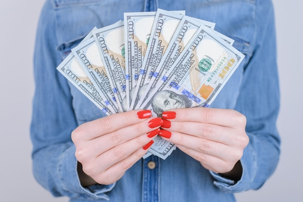 Красная стопка пачки людей человек новый налоговый обмен валюты клиент покупатель образ жизни переносим мы даем концепцию. обрезанное крупным планом фото дамы, держащей деньги в руках, изолированные на сером фоне