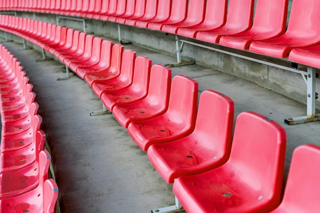 Red stadium seats after rain. soccer, football or baseball stadium tribune without fans.
