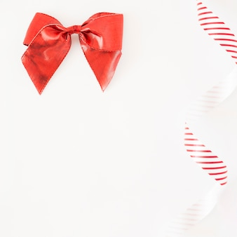 Red stain bow and striped ribbon on white background