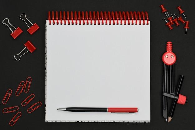 赤い文房具と黒の背景の空白のスパイラルノート。文房具セット。幾何学的な図面のコンパス、ペーパークリップ、ペンで白い紙のノートの周りの文房具のピン。