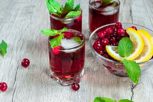 Red stemware shot alcoholic cold cocktail with cranberries raspberries lemon and mint