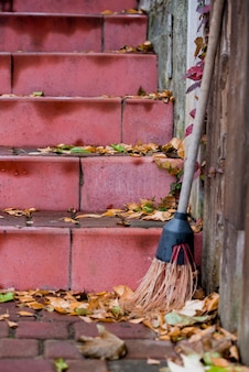 Red steps with yellow foliage, broom, yard cleaning.