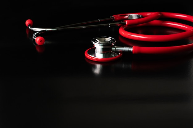 Red stethoscope on black background. healthcare and medicine concept