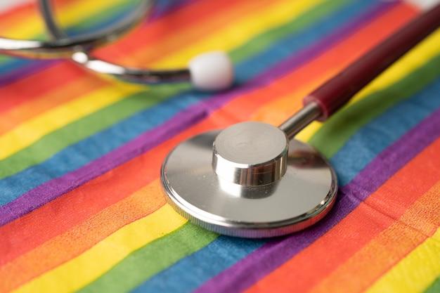 虹色の旗の背景に赤い聴診器。