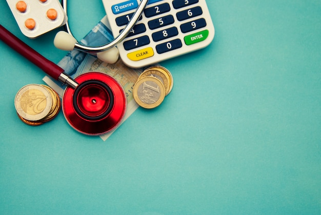 Red stethoscope on a pile of coins, pills over blue . copyspace. medicine and health care.