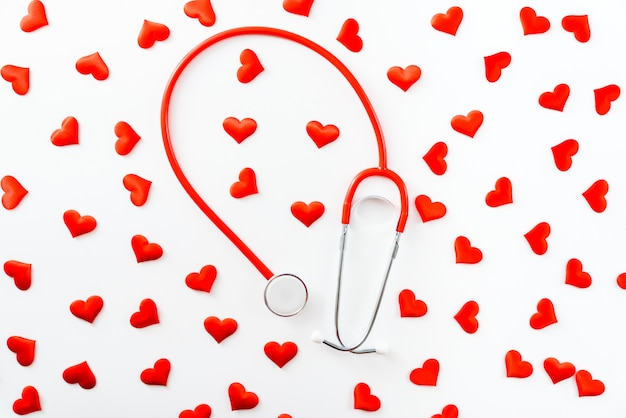 Red stethoscope surrounded by hearts seen from above isolated on white