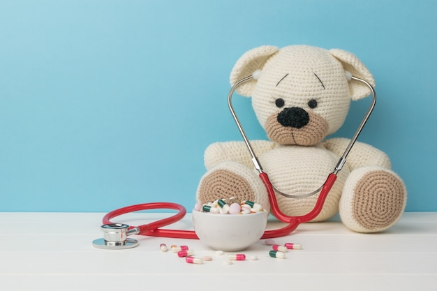 A red stethoscope on a white knitted bear and pills in a bowl.