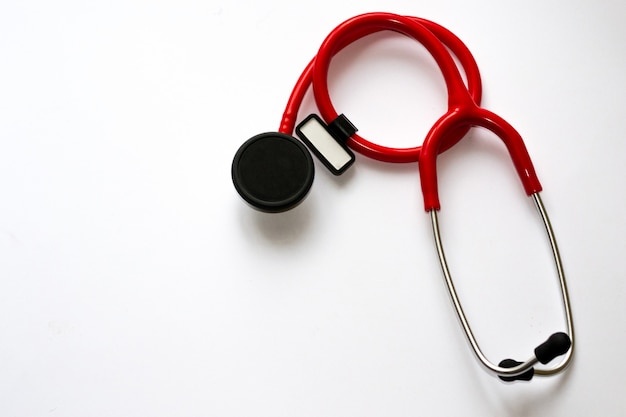Red stethoscope with black membrane and white sticker isolated on white background