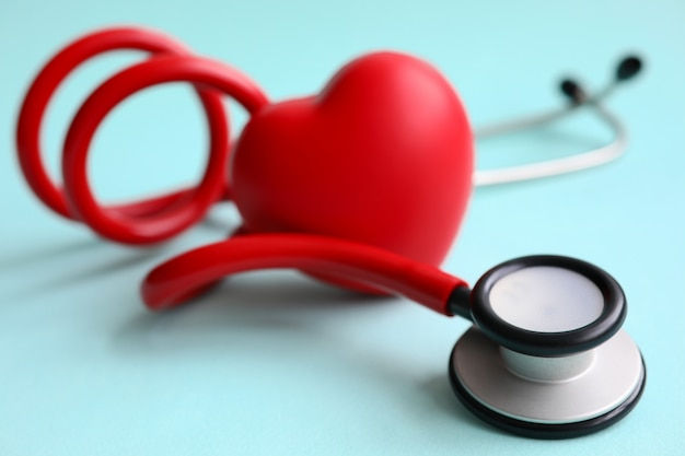 Red stethoscope with heart on blue modern background. medical insurance concept