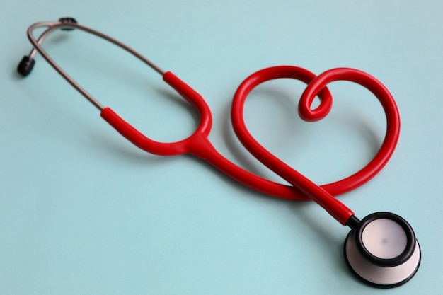 Red stethoscope with heart on blue modern background