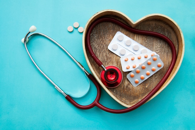 Red stethoscope with tablets, pills on blue . copyspace. medicine, heartbeast .