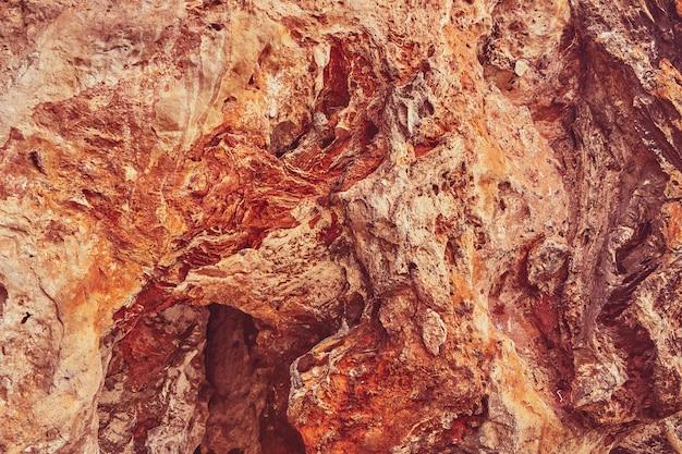 背景として赤い石の洞窟の壁