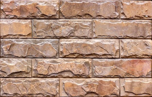 砂岩のタイルで飾られた赤い石の壁。背景またはテクスチャ
