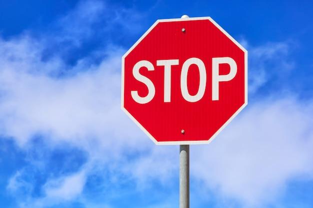 Красный знак остановки на синем фоне облачного неба