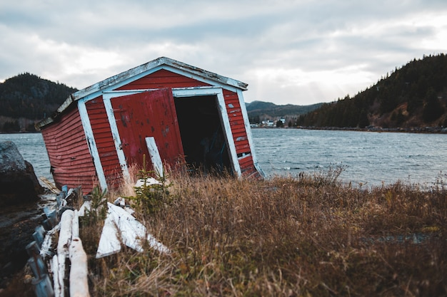 Red storage shed near body of water