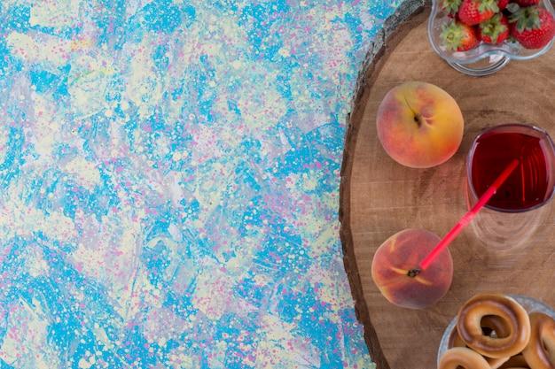 Красная клубника и персики со стаканом сока и печеньем на деревянном блюде