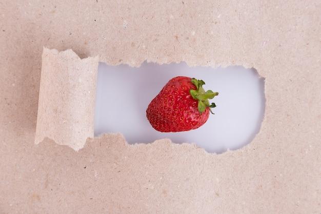 一枚の紙とベージュの情熱のシボルとしての赤いイチゴ