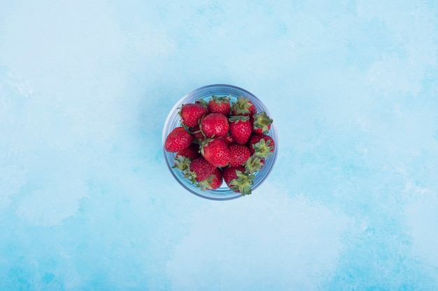 Red strawberries in a glass cup on blue