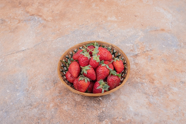 Красная клубника в глиняной посуде на мраморе