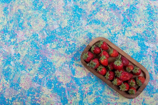 Красная клубника в деревянном блюде на синем столе, вид сверху