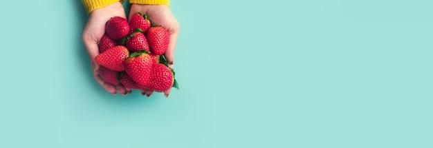 Красная клубника в руках на синем фоне, летние ягоды
