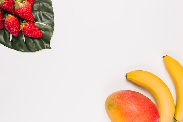 Red strawberries on monstera and banana with mango in corner on white background