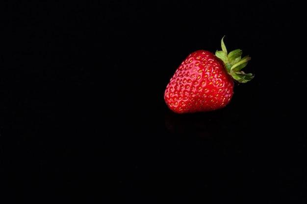 黒の背景に赤いイチゴ。甘い生活のコンセプト。