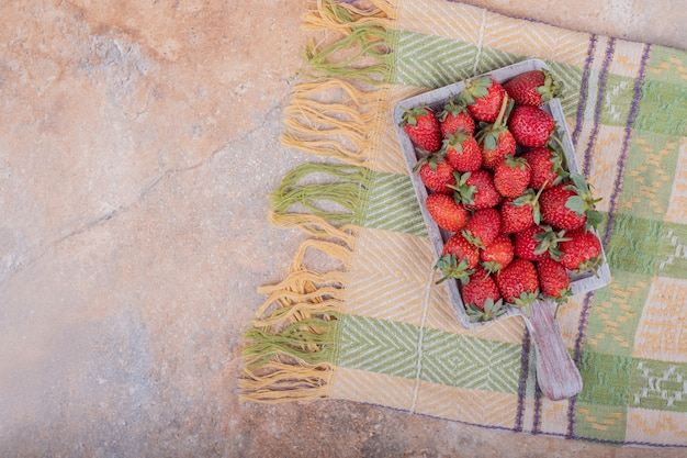Red strawberries in a rustic wooden platter on the marble