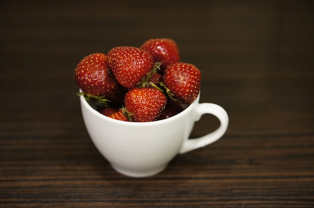 Red strawberries in a white cup