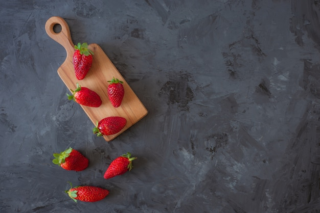Red strawberries on wooden plate on black background , top view , flatlay with copy space