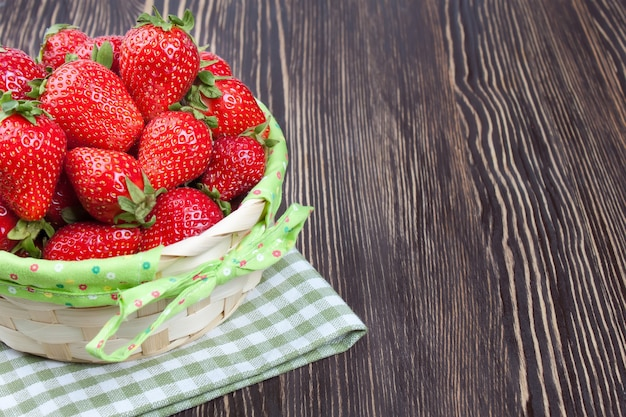 Red strawberry in a basket on brown wooden table