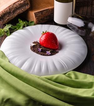 大きな白いプレートにチョコレートチップとスミレが入った赤いイチゴのデザートケーキ。