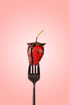 Red strawberry on a fork with melt chocolate.