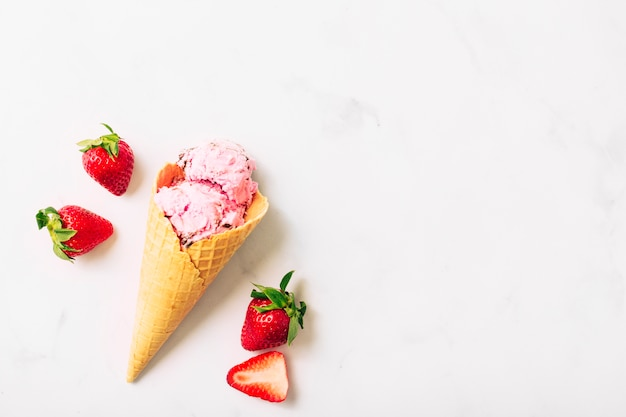 Red strawberry and fruit ice cream in waffle cone