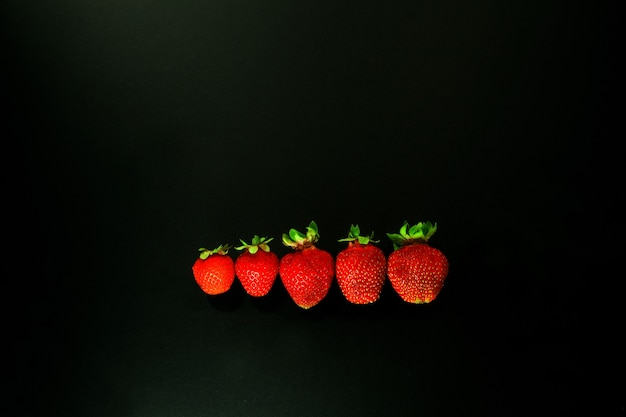 Красный клубничный на черном фоне. красные strawwberies в линии