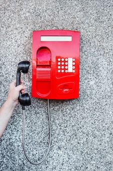 Red street pay phone on the wall and a man's hand picking up the phone