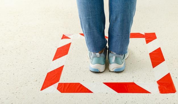 사회적 거리를 유지하기위한 빨간 줄무늬 선 기호입니다. 코로나 19 격리 중 경고 선 뒤에 서있는 여성.